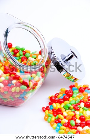 vertical cropped view of clear open jar and pile of jelly beans
