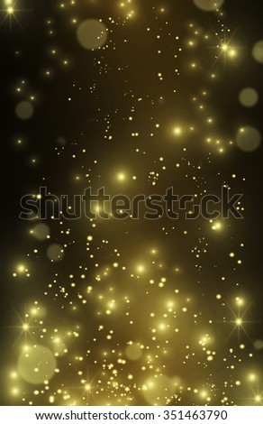 Vertical festive glittering wallpaper, perfect for party invitation. Beautiful gold glitter stars and star dust. Gold effect pixie dust on black. Bokeh golden background with shining sparkles and sand