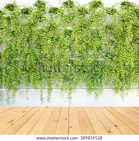 vertical green plant pattern in many black pot on wood floor background - stock photo