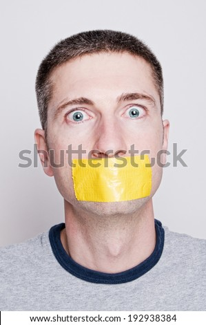 Vertical headshot of adult man with yellow duct tape over mouth - stock photo