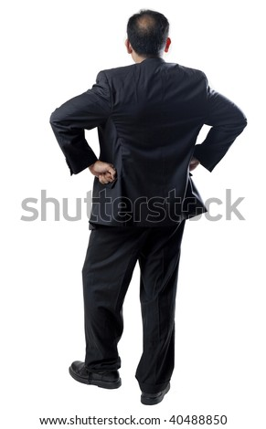 Vertical image of a balding man with arms akimbo in a business suit.