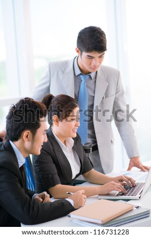 Vertical image of a business group working on project in office