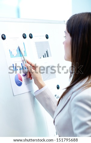 Vertical image of a businesswoman pointing at the financial document attached to a whiteboard - stock photo
