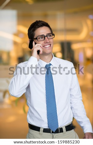 Vertical image of a cheerful businessman talking by phone inside - stock photo