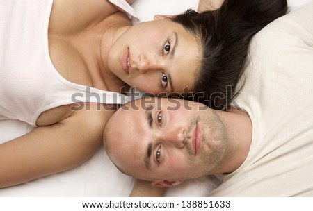 Vertical image of a couple lying head to head