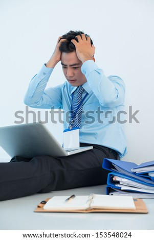 Vertical image of a depressed businessman sitting on the floor with pile of documents while networking on the foreground - stock photo