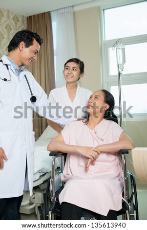 Vertical image of a doctor and a patient sitting in the wheel-chair - stock photo