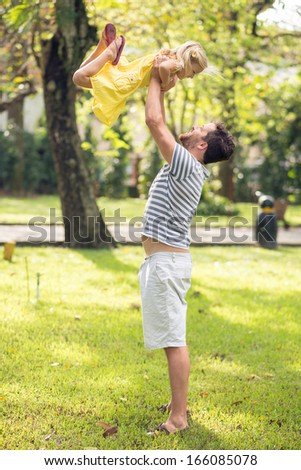 Vertical image of a father having fun with his daughter in the park - stock photo