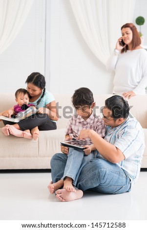 Vertical image of a father learning his son to use modern gadget on the foreground, a senior sister reading with a junior sister  - stock photo