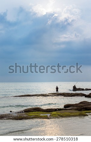 Vertical image of a fisherman who is standing alone at the seashore at morning sunrise background. - stock photo