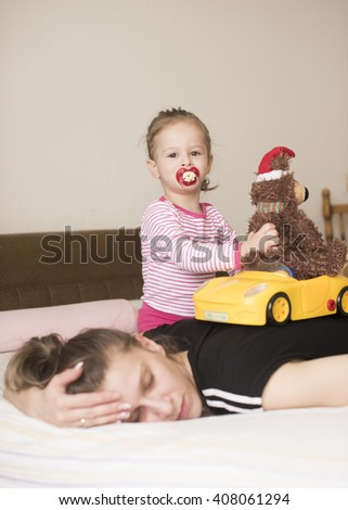 vertical image of a little girl playing with a yellow toy car and a fluffy brown teddy bear with Santa hat on the bedroom bed in her pajamas and pacifier in her mouth while her mother takes a nap - stock photo