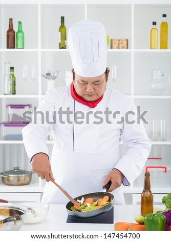 Vertical image of a mature cook frying vegetables in the frying-pan - stock photo