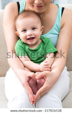 Vertical image of a mom holding her little son and showing a heart sign on the foreground - stock photo