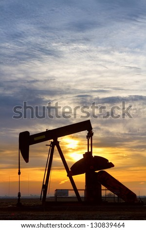 Vertical image of a oil pump jack at a golden sunrise. - stock photo