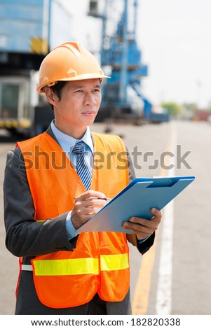 Vertical image of a port manager in protective uniform with clipboard  - stock photo