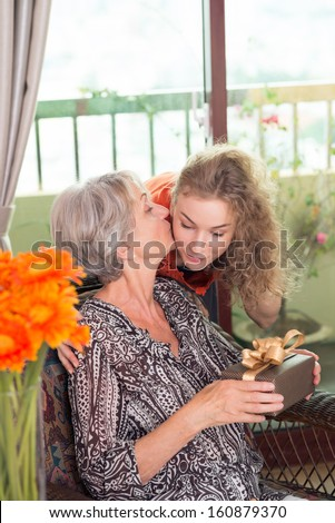 Vertical image of a pretty granddaughter giving a present and a kiss to her granny - stock photo