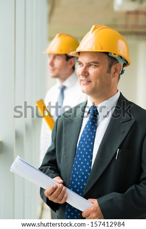 Vertical image of a professional engineer with a draft in hands on the foreground - stock photo