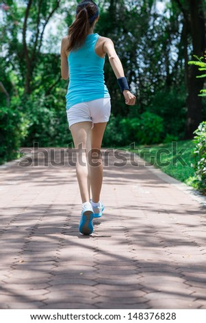 Vertical image of a running young girl viewed back - stock photo