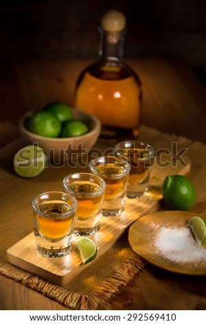 Vertical image of a serving of gold Tequila shots spread out and ready to drink at a party