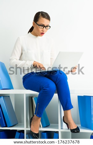 Vertical image of a surprised businesswoman sitting on the cupboard at the office and networking  - stock photo