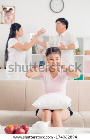 Vertical image of a teenage girl covering her ears while her parents quarreling on the foreground  - stock photo