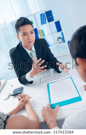Vertical image of a young banker explaining something with enthusiasm to his clients on the foreground - stock photo