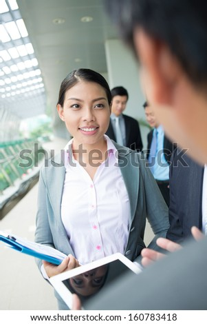 Vertical image of a young business lady listening to his colleague with interest on the foreground