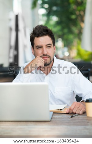 Vertical image of a young businessman contemplating at a cafe - stock photo