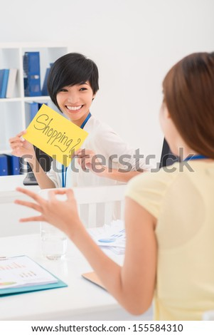Vertical image of a young businesswoman showing a 'Shopping?'?� placard while her colleague showing her an 'okay'?� gesture on the foreground - stock photo