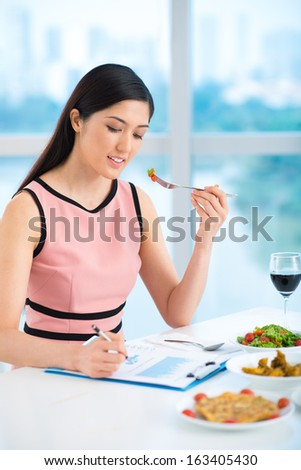 Vertical image of a young businesswoman working while her lunch inside - stock photo