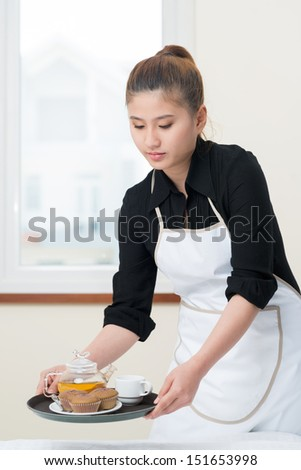 Vertical image of a young chambermaid preparing breakfast for the guests  - stock photo