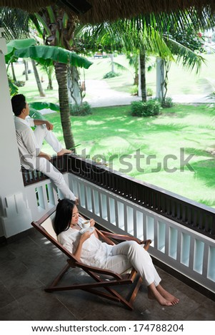 Vertical image of a young couple relaxing in resort  - stock photo
