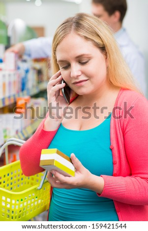 Vertical image of a young customer choosing the treatment while talking by the cell phone in the drugstore on the foreground - stock photo