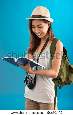 Vertical image of a young traveler standing with a map-book and choosing the way on the blue background