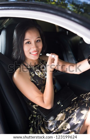 Vertical image of an elegant lady applying lip balm in car