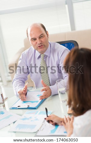 Vertical image of an emotional boss explaining something to his colleague at the office on the foreground  - stock photo