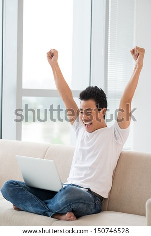 Vertical image of an excited young man networking at home - stock photo