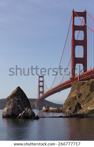Vertical image of big sea rocks near Golden Gate bridge with old lighthouse and fog station under the bridge in soft morning light. San Francisco. California. USA
