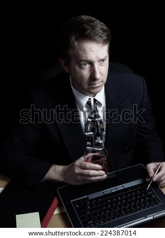 Vertical image of business man, looking at computer screen, working late with black background  - stock photo
