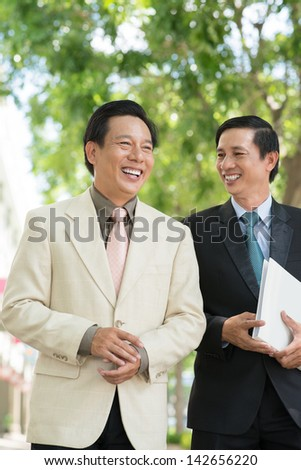 Vertical image of businesspeople laughing at something outside - stock photo