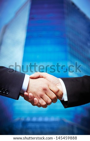 Vertical image of entrepreneurs concluding a deal with a skyscraper in the background - stock photo