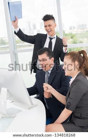 Vertical image of excited co-workers sitting in front of the computer