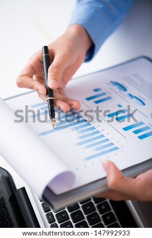 Vertical image of female hands analyzing business strategy constructively
