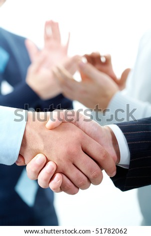 Vertical image of handshake on the background of applause of colleagues
