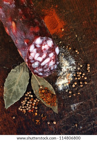 Vertical image  of  italian salami with spices on wood cutting board - stock photo