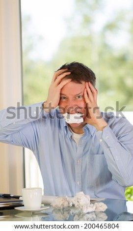 Vertical image of mature man showing stress by biting wad of paper while working from home with bright daylight coming in from window in background - stock photo