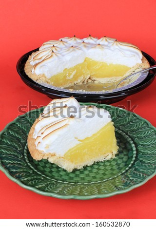 Vertical image of serving of lemon meringue pie on green plate with sliced pie in background. - stock photo