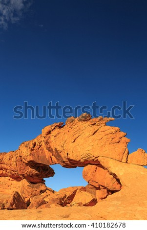 Vertical image of Sunset Arch in the Utah desert, USA. - stock photo
