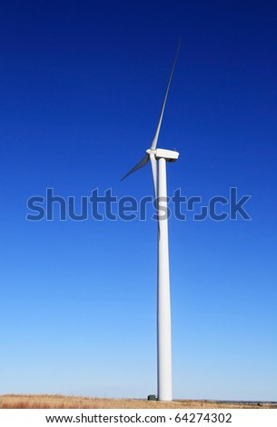 vertical image of tall white electric windmill or wind turbine on a flat prairie with blue sky background