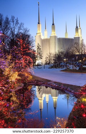Vertical image of the majestic Latter Day Saints Mormon Temple reflecting in the water of a small pond where shrubbery is decorated to celebrate the holiday season in metropolitan Washington, DC. - stock photo